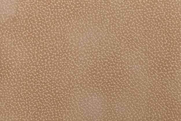 動物のコートで飾られた薄茶色の布の群れの背景。糸くずの出ない布。