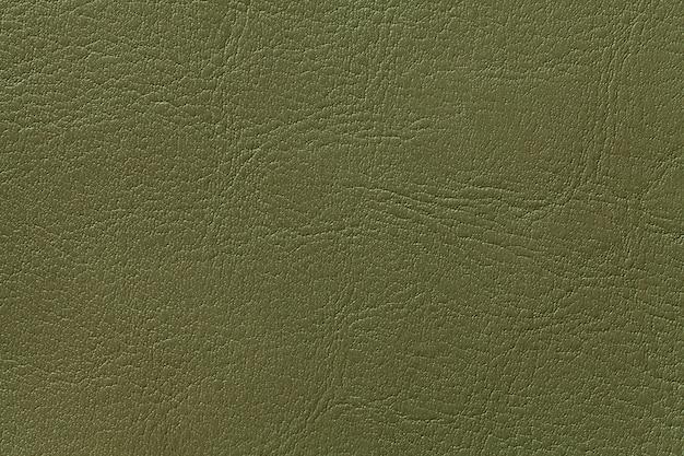 ダークオリーブレザーのテクスチャ背景、クローズアップ。緑のひびの入った背景