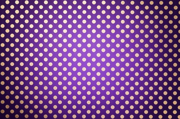 銀の水玉のクローズアップのパターンで包装紙から暗い紫色の背景。