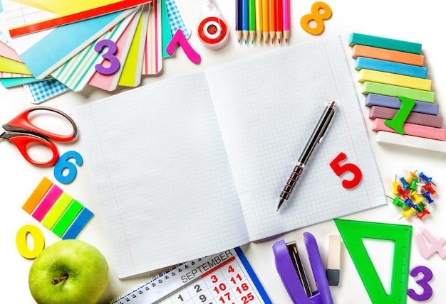 Откройте пустой блокнот с ручкой в центре рамки. различные канцтовары.
