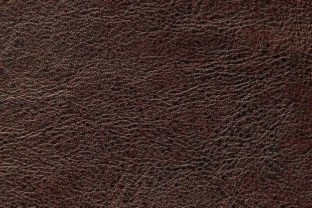 ダークブラウンレザーテクスチャ背景、クローズアップ。しわ肌から青銅ひびの入った背景