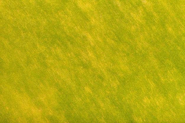 フェルト生地の明るい緑と黄色の背景。ウール織物のテクスチャ