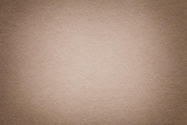 古い光の茶色の紙の背景、クローズアップの質感。濃いベージュのボール紙の構造。