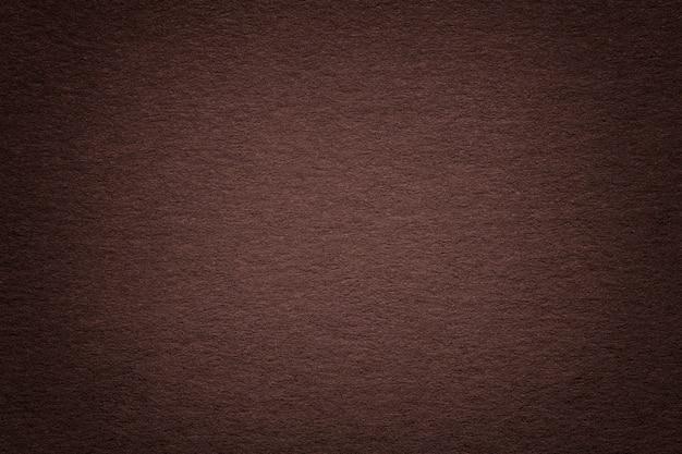 古い暗い茶色の紙の背景、クローズアップのテクスチャ。濃いベージュのボール紙の構造。