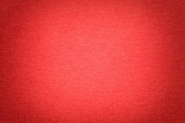古い鮮やかな赤い紙の背景、クローズアップの質感。密集したボール紙の構造