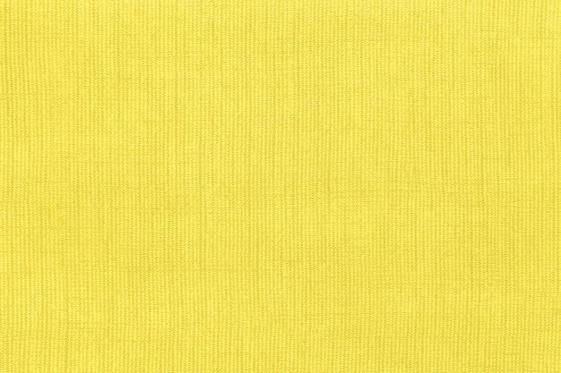 パターン、クローズアップで繊維素材から黄色の背景。自然な風合いの生地の構造。