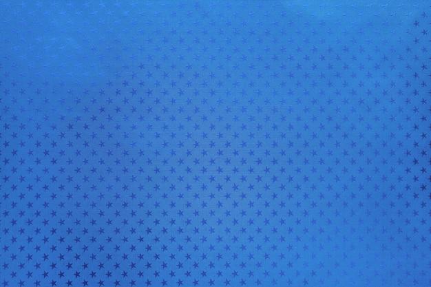 星のパターンを持つ金属箔紙から青い背景