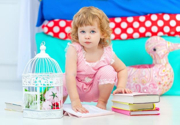 子供の寝室の床に座って本を見てピンクのパジャマでかわいい巻き毛の少女。
