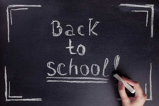 女性の手が黒い黒板に白いチョークで「学校に戻る」というフレーズを書く。