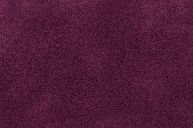 濃い紫色のスエード生地のクローズアップの背景。ワインヌバックテキスタイルのベルベットマットテクスチャ