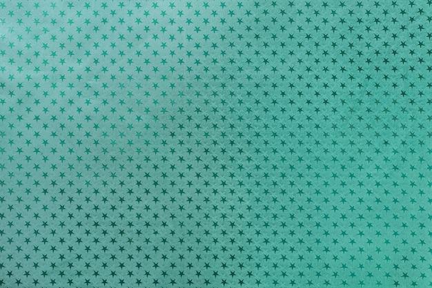 星のパターンを持つ金属箔紙から暗い青緑色の背景