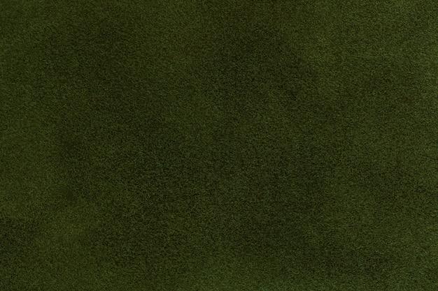 濃い緑色のスエード生地のクローズアップの背景。オリーブヌバックテキスタイルのベルベットマットテクスチャ