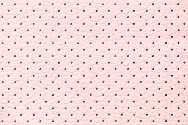 穴あきピンクの革の質感の背景、クローズアップ