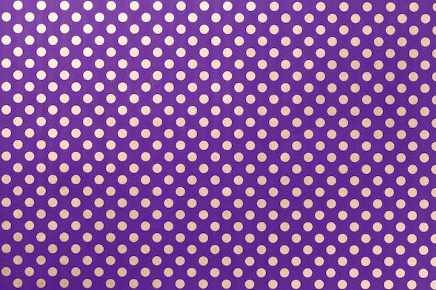 銀の水玉のクローズアップのパターンを持つ包装紙から暗い紫色の背景