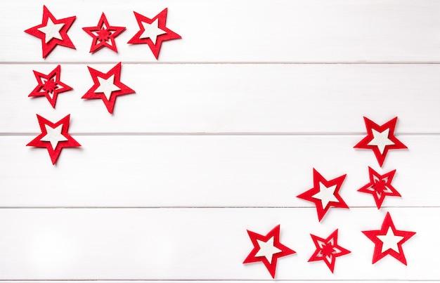 白い木製の背景に赤い星とクリスマスフレーム。