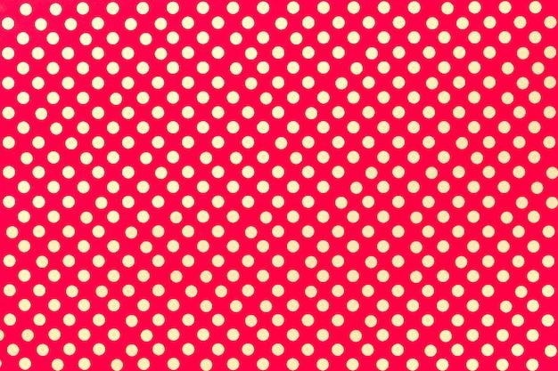 黄金の水玉のクローズアップのパターンを持つ明るい赤の包装紙。