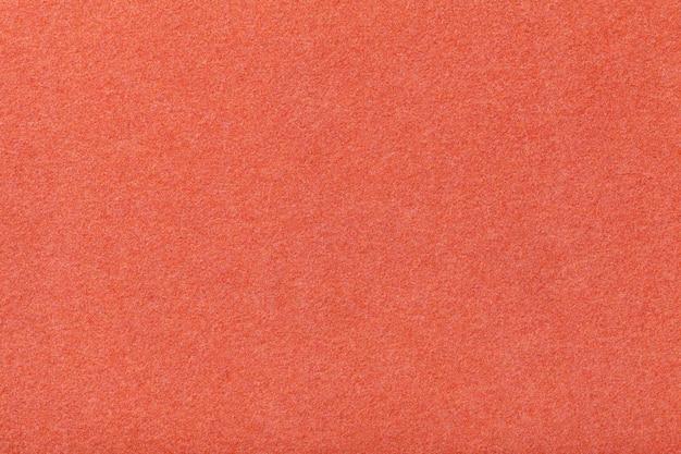 ダークオレンジのマットスエード生地のクローズアップ。フェルトのビロードの風合い。