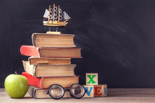 古い教科書は、黒チョークボードの背景に素朴な木製のテーブルにあります。