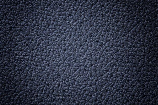 穴あきネイビーブルーレザーテクスチャ背景、クローズアップ。しわ肌からデニムの背景。