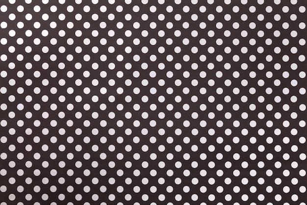 白い水玉のクローズアップのパターンを持つ包装紙から黒の背景。