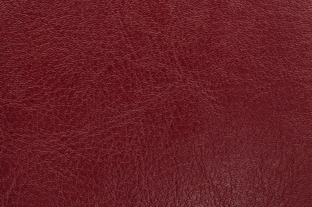 濃い赤革のテクスチャ背景。クローズアップ写真。