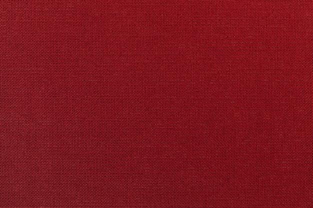 繊維材料からの濃い赤の背景。自然な風合いの生地。背景。