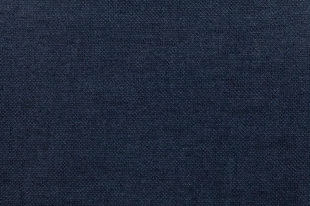 繊維材料からの暗い青色の背景。自然な風合いの生地。背景。
