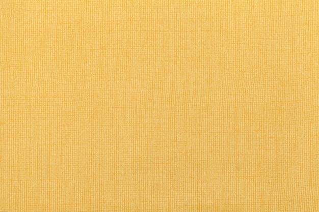 繊維材料からの明るい黄色の黄土色の背景。自然な風合いの生地。背景。