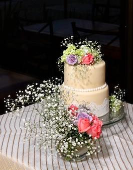 テーブルの上に花とウエディングケーキ