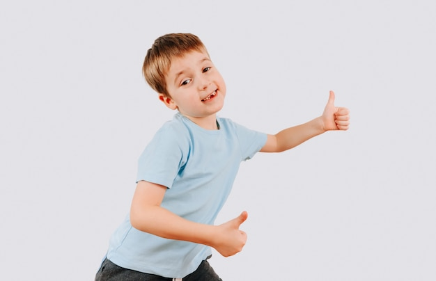 Портрет счастливый улыбающийся малыш мальчик, давая пальцы жест рукой