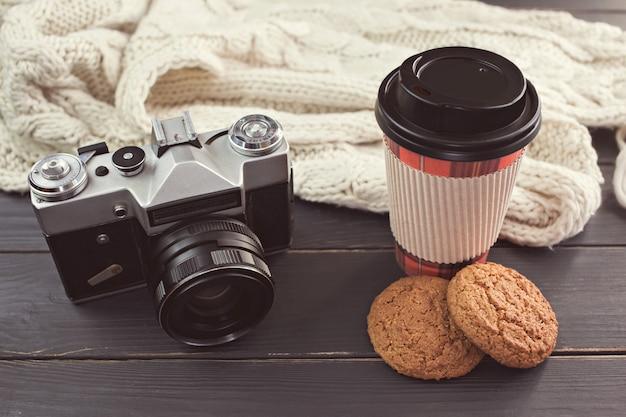 Горячий кофе, овсяное печенье, ретро фотоаппарат и шарф на черном столе. тонировка.