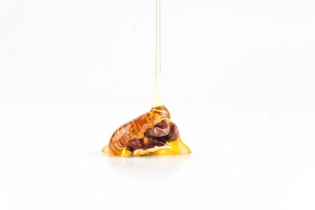 白い背景で隔離の甘い蜂蜜とクルミ