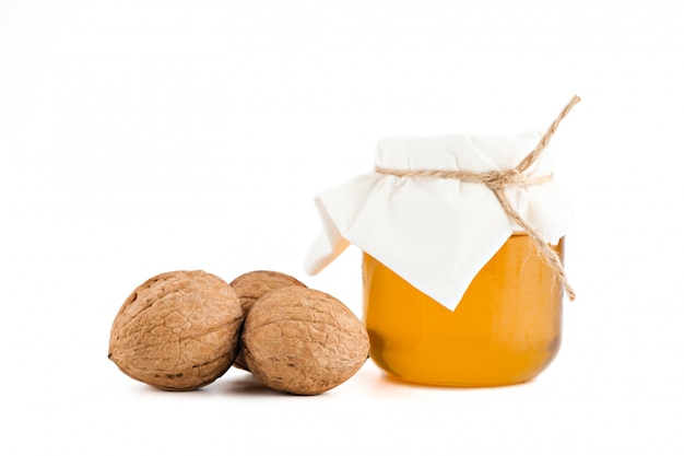 蜂蜜とクルミの白い背景で隔離のガラスの瓶
