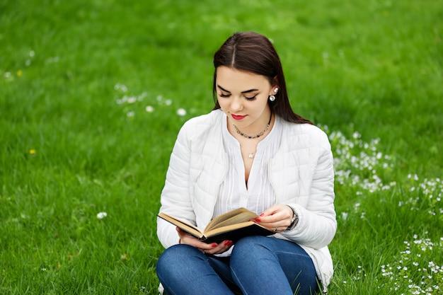 Красивая женщина сидит на траве и читает книгу