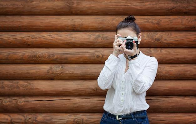 Фотограф молодой женщины в белой блузке и синих джинсах делает фото на старой ретро пленочной камере.