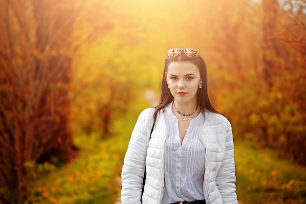 日当たりの良い黄色の葉の上の秋のファッションの肖像画の女性