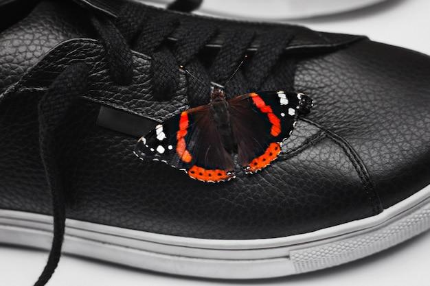 Красивая бабочка на черных кожаных кроссовках. натуральная и стильная концепция. выборочный фокус. закрыть