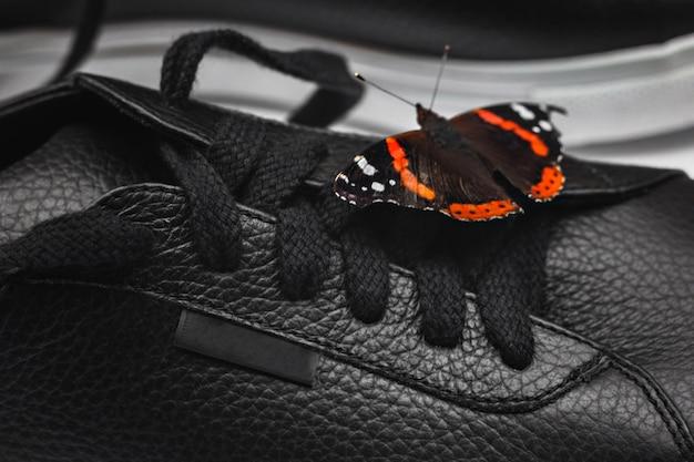 Красивая бабочка на черных кожаных кроссовках. блоггер или стильная концепция. выборочный фокус. закрыть