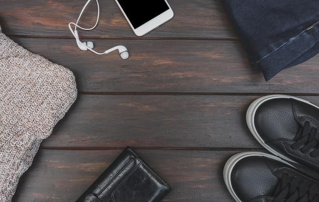 コピースペースを持つ木製テーブルに秋や冬の布とアクセサリーのフラットレイアウト。ウールのセーター、ヘッドフォン付き携帯電話、ブルージーンズ、レザースニーカー、財布