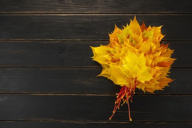 Осенний букет из кленовых листьев на черном деревянном столе