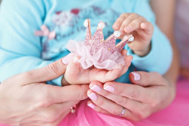 女の赤ちゃんと小さなピンクの王冠を保持している母親