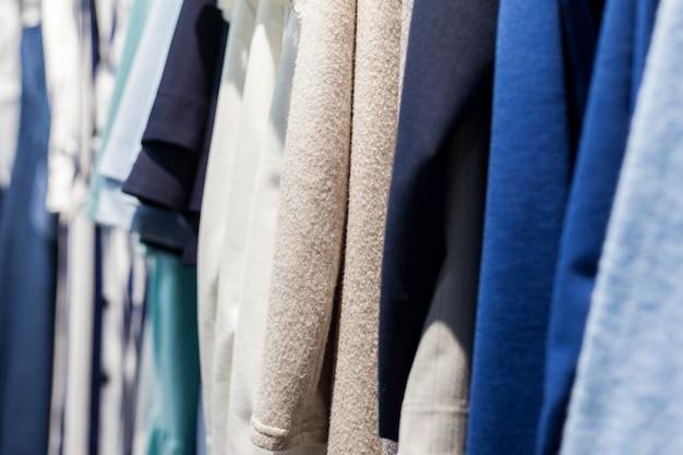 Разная одежда на вешалках крупным планом в магазине одежды