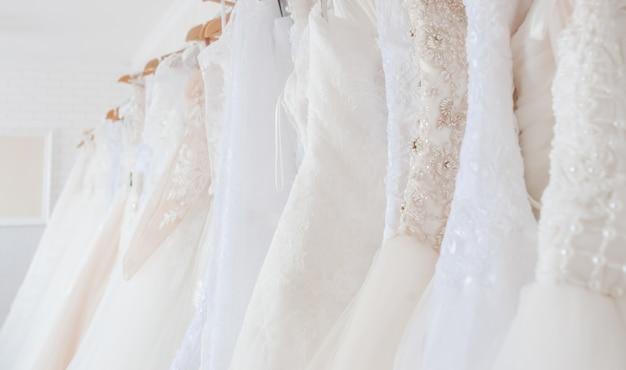 ハンガーに掛かっているウェディングドレス。ブライダルサロンのインテリア。