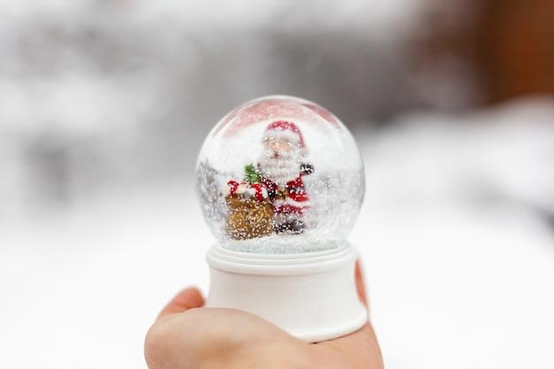 Рождественский снежный шар в руке