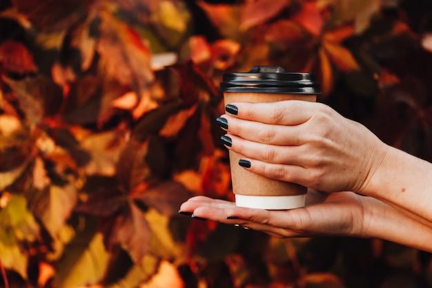 秋の通りで美しい少女は、彼女の手で温かい飲み物とカップを保持しています