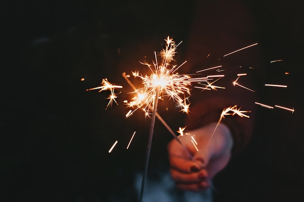 Рождественский бенгальский огонь на темноте. бенгальский огонь