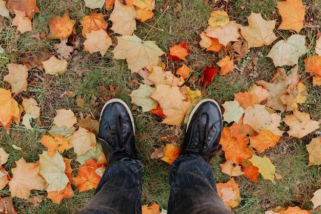 Ноги в сапогах на осенних листьях