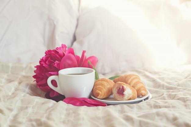 コーヒーカップ、クロワッサン、花の朝食
