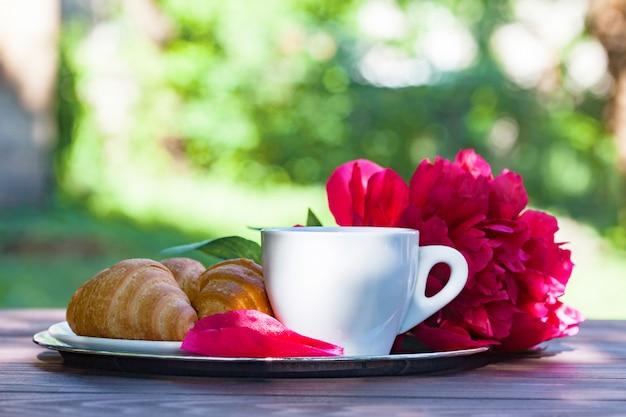 一杯のコーヒー、クロワッサン、牡丹の花の花束