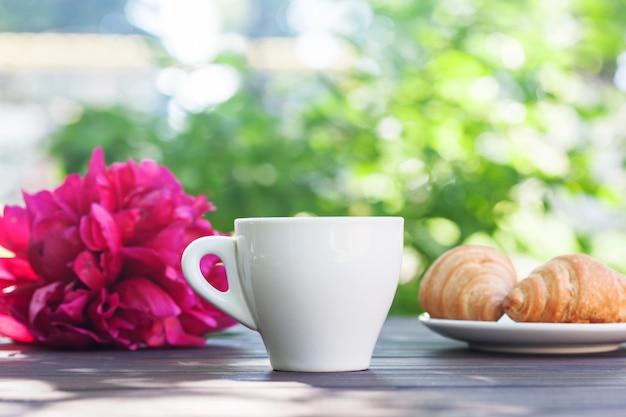 一杯のコーヒー、クロワッサン、朝の庭の木製のテーブルの花